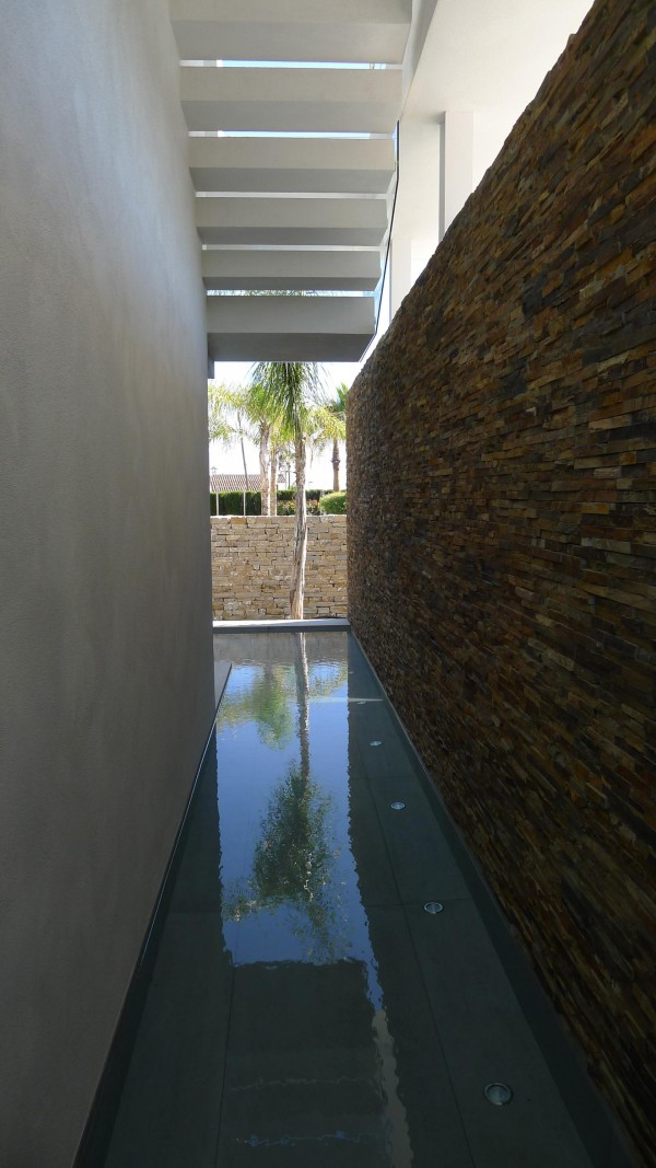 A small channel of water wraps around the house, another reminder of this home's connection to its Mediterranean environment. At night, the underwater lights scatter sparkling reflections against the home and the surrounding privacy wall.