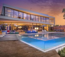 A smooth white facade folds around transparent glass volumes, the top half slightly offset in relation to the ground floor. An angular terrace divides the two floors and overlooks the spectacular pool and patio below.
