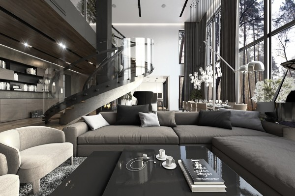 The living room is more open and bright, occupying a double-height space centered by a spectacular spiral staircase leading to a private mezzanine. A wall of books stands on the left, a dining space in the background on the right. The attention to detail is very pronounced in this space: even the series of lights over the dining table reflects the shape of the wineglasses below.