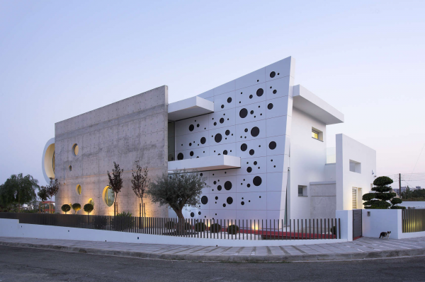 This perforated building (located in Nicosia, Cyprus) is a striking blend of angular construction and playful port windows. Not pictured - but alluded to on the left - a u-shaped fold gives the back of the home an open and organic aesthetic that smartly contradicts the sharp facade.
