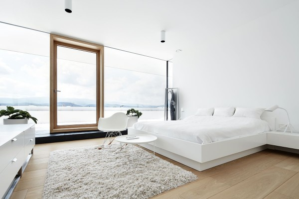 No ornamentation, no color, only a spectacular view of the water outside – the wood frame door appears to float within a void as if there is no exterior wall at all. Even the bed seems light as a cloud, with a slightly recessed base and cantilever side table.