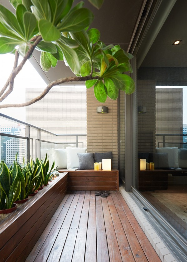 Outside the living room, a beautiful covered terrace acts as a miniature backyard, complete with wooden decking and verdant plants. The built-in seating looks like a comfortable place to relax and watch as people go about their days on the streets below.