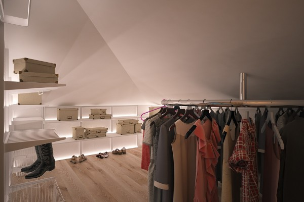 A hidden walk-in closet takes advantage of indirect lighting for a luxurious showroom effect.