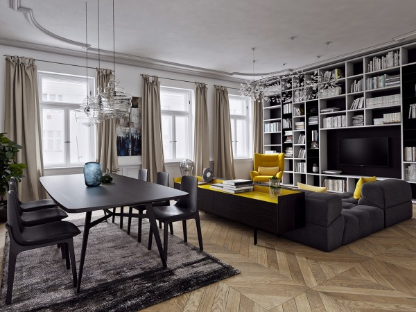Luxurious matte black and stark white decor yields to the brightness of carefully-chosen yellow accents, like the sideboard table and the sofa throw pillows. Taking center stage is the bright yellow Nikos chair by Sergio Bicego.