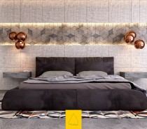 Gorgeous! This bedroom makes an immediate visual impact with rough textured concrete in a sharp geometric pattern, with oversized headboard panels above and below. Copper lamps from Tom Dixon hover above the cantilever bedside tables (also concrete) and a bright patterned rug energizes the color palette.