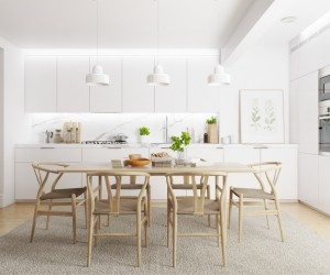 White walls and cabinetry allow the dining arrangement to stand out with emphasis, the natural wood of the simple table and iconic Wishbone chairs serving as a strong contrast to the minimalistic materials used throughout.