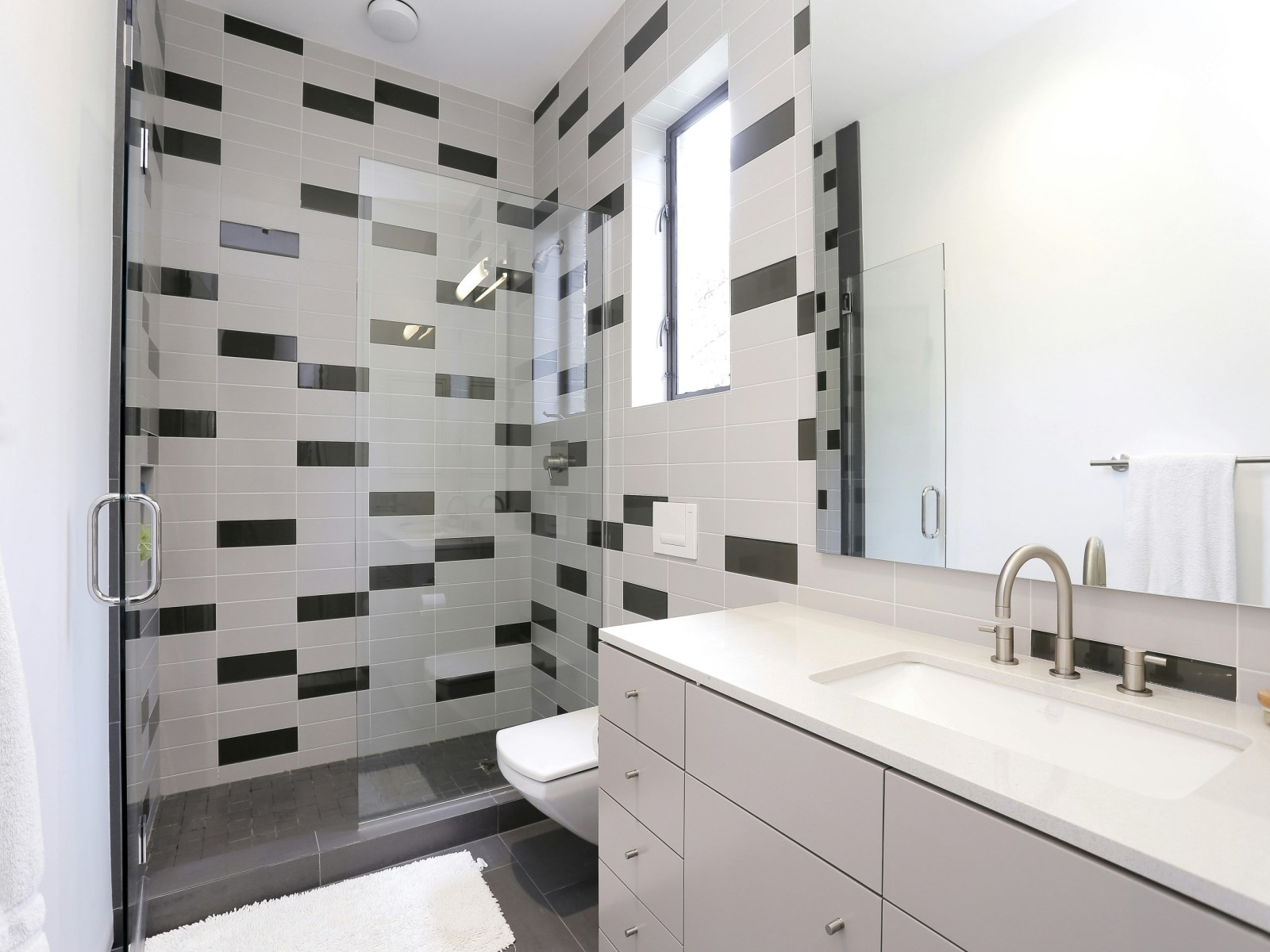 Black And Gray Tile Bathroom - A home with formidable architecture and a light interior