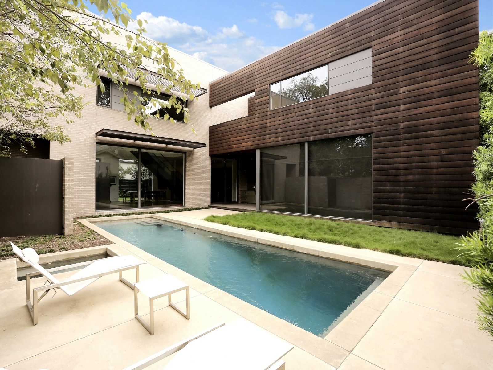 Brick Concrete And Wood Pool Deck - A home with formidable architecture and a light interior