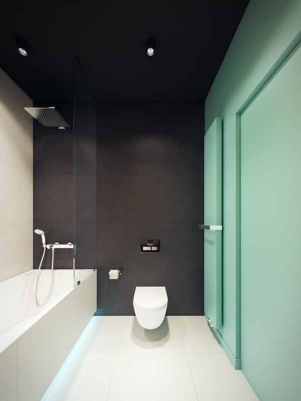 Additional blue accents energize the bathroom. The bold interplay between matte black tiles, clean white surfaces, and an adventurous color accent wall contribute to a sharp and clean atmosphere.