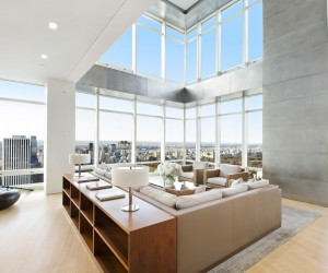 This Manhattan penthouses boasts massive windows with sweeping views of the famous New York skyline. The designers have done a fantastic job not only focusing the furniture so it can take advantage of these views, but they've sectioned off the living space with a L shaped couch and a low bookshelf. Both tips you can use in your own space!