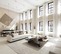 """This apartment occupies a generous 6,471 square foot floor plan centered on a great room with a double-height ceiling, its lovely neutral interior flooded with light from windows that span the 17'5"""" walls. The current design maintains the characteristic industrial details from the property's former life, setting the stage for a glamorous modern interior in line with today's minimalist tastes. Track lighting, spectacular chandeliers, and eye-catching artwork offer abundant interior decor inspiration."""