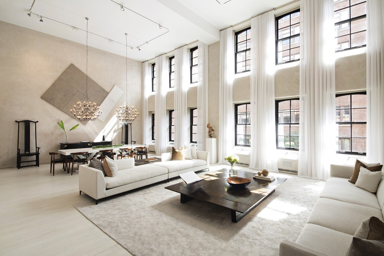 "This apartment occupies a generous 6,471 square foot floor plan centered on a great room with a double-height ceiling, its lovely neutral interior flooded with light from windows that span the 17'5"" walls. The current design maintains the characteristic industrial details from the property's former life, setting the stage for a glamorous modern interior in line with today's minimalist tastes. Track lighting, spectacular chandeliers, and eye-catching artwork offer abundant interior decor inspiration."
