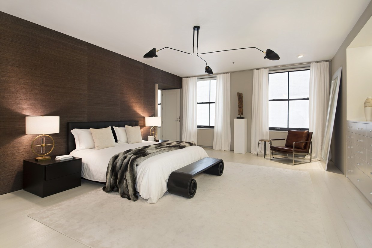 A sculptural Serge Mouille three-arm chandelier serves as the primary overall lighting for this refined bedroom. The silky wooden wall panels behind the headboard serve as a good blank canvas for self-expression.