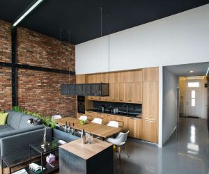 This space blends the industrial with the organic seamlessly, and you can see that here in the open kitchen living space. The brick wall is quintessential for an industrial space, but mixed with the warm wood cabinets and the scattered plants, this space is infused with a bit of nature.