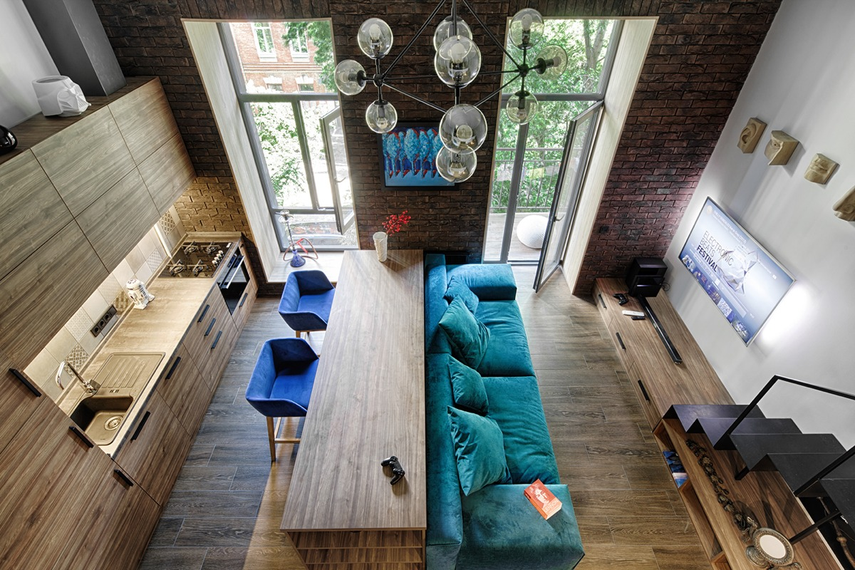 A 49-metres-squared loft in Kiev by Ivan Yunakov (http://yunakovdesign.com) alsouses signature shades to create harmony in cosy spaces. High-ceilinged brick andpanelled wood fixtures afford the height for long-lined doors, which are stretchedhorizontally by similar-shaped benches. A turquoise couch with electric blue suedesingle seats offer seats to look at bauble lighting, the only rounded fixture in the room.