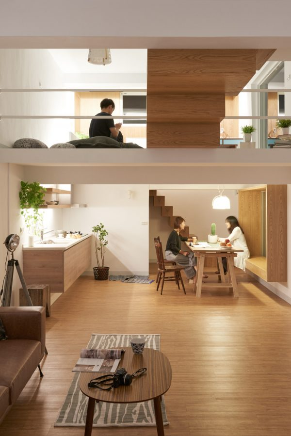 As the day darkens, main living spaces take on alternate functions. The kitchen table turns into dinner. The bedroom's low-lying furniture affords a view up a level, and lighting illuminates over surfaces, drawing attention away from their casing fixtures. A white rail ensures safety without structural interference.