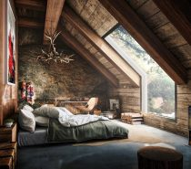 This rustic attic bedroom is striking. The chandelier made from antlers is lit up by the natural light let in by the large window. Wooden walls and a wood burning fireplace make this space so cozy.