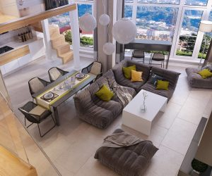 Looking down on this gray and white loft you can see that there is a lot going on in this open floor plan. A dining table and chairs buts up against a floating couch. There is more seating facing the large white framed windows and you can see a glimpse of the kitchen in the back.