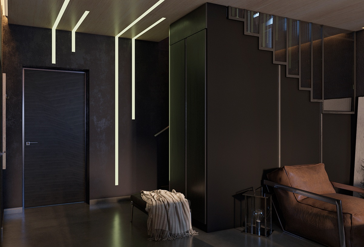 Matte-textured walls lead out of the living room to an entrance corridor striped in light. LED lights of different lengths shine through, wall to ceiling, wall to floor. Charcoal-hued cabinetry in the kitchen provides a clean surface to impact.