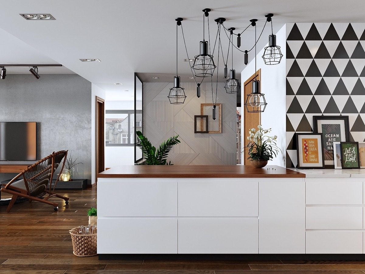 The kitchen, on closer inspection, ties in the rest of the room. A bold triangular wallpaper mirrors the subtle geometric pattern textured on the silver entrance wall. Hanging lights are matched by steel-framed stools. Inset marble tiling and colourful leaning pictures add colour to a space to bind them all.