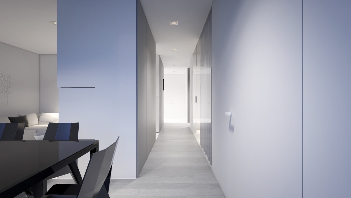 Further down the corridor, the entrance makes its first appearance. Hugged by the corridor's grey walls, a small seating inlet backed by a mirror welcomes in first-time guests. A ringed tree trunk stump, an unusual shape in the space, sits fiercely on the incoming wall.