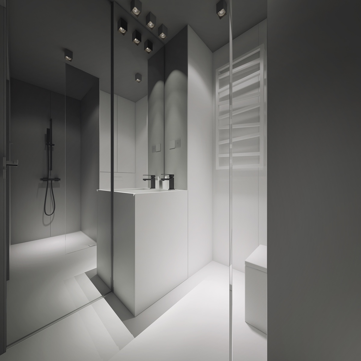 The ensuite is also made roomy by minimalism. Using floor-length mirrors and white block porcelain, the space creates room within a feeling of calm. Simple chrome fixtures and all-grey walling give the bathroom depth. Simple features in the black shower head and zig-zag heated towel rail add sophistication without clutter.