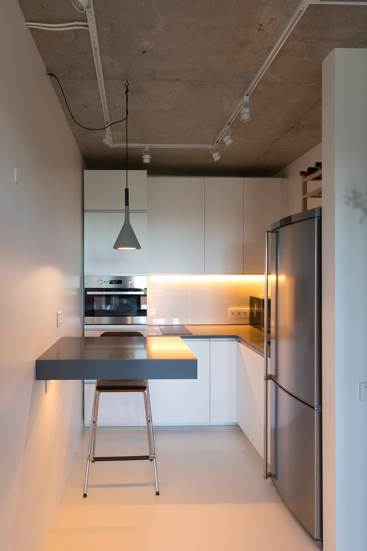 http://cdn.home-designing.com/wp-content/uploads/2016/10/Minimalist-kitchen-white-walls-industrial-ceiling-grey-hanging-light-and-ledge-table.jpg
