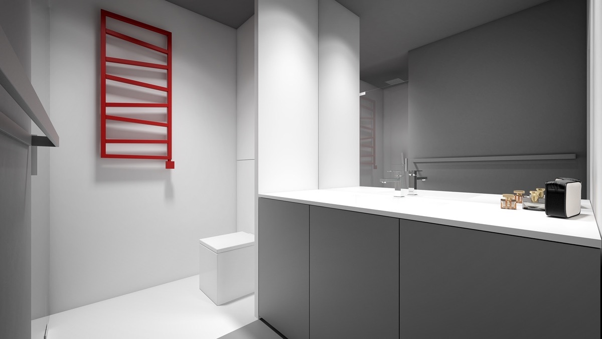 A red heated towel rail is the first to break colouring in the bathroom. Sitting flat upon amongst dark grey cabinetry and white porcelain fixtures, its presence is dominant, but not cluttered. A chrome towel rail and taps add pizazz.