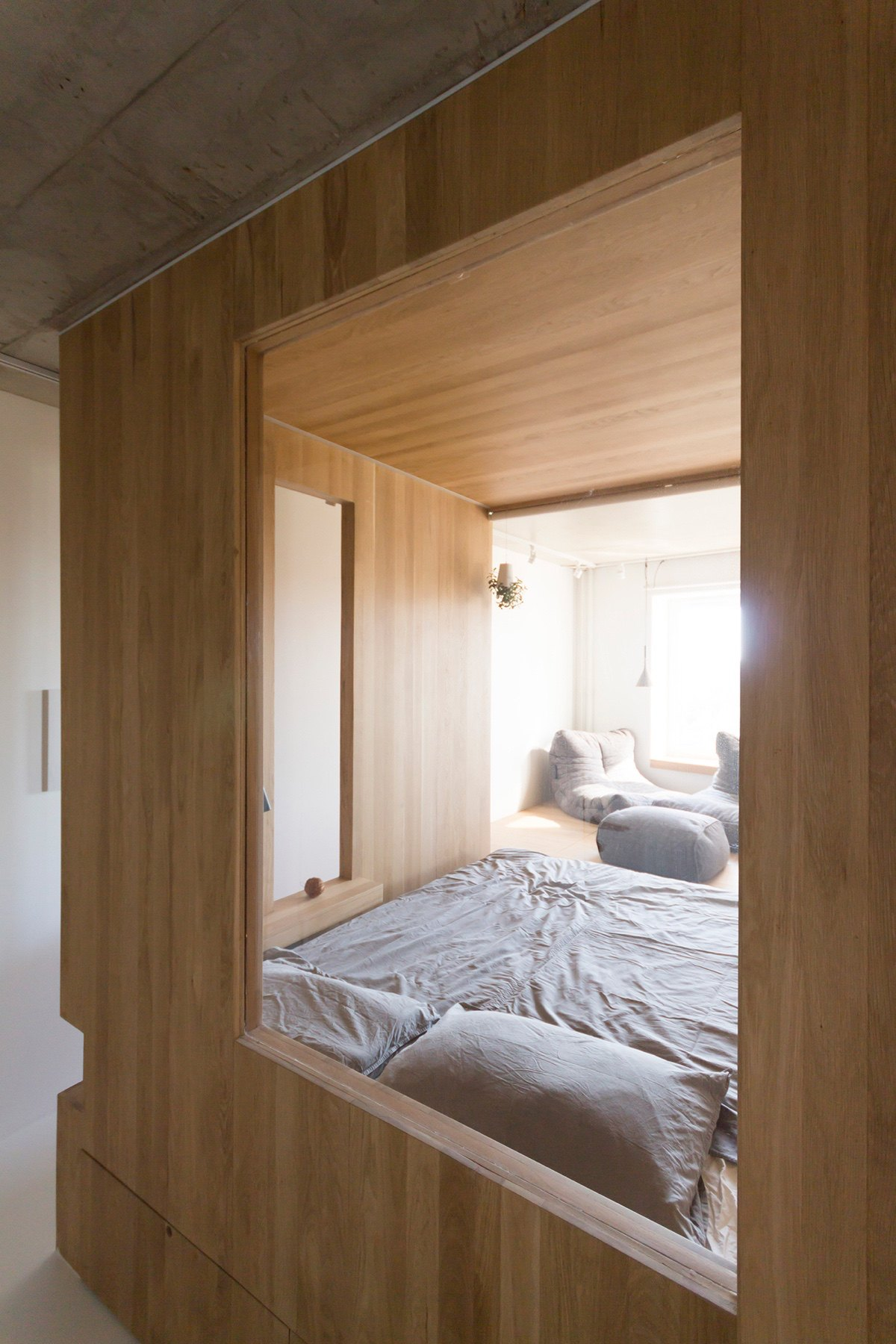 View Through Inner Bedroom Window Grey Bedding White And Wooden Walls - Super small studio apartment under 50 square meters includes floor plan