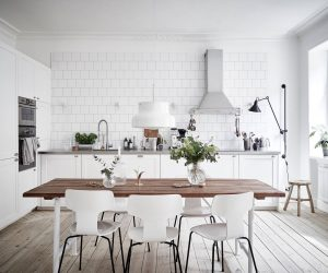 White brick and cabinetry open a light and bright space dotted with white accessories, a central wooden table, black stencil legs and lighting.