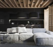 Let's start with a home that uses black-on-black design. Variations help define the boundaries of each part of the open plan living space, drawing attention to the white sofa or the warm grey dining arrangement. The furniture and accessories in each functional space sets a specific mood: the kitchen is luxurious, the dining space is moody, and layered textures around the sofa set a casual and comfortable tone.