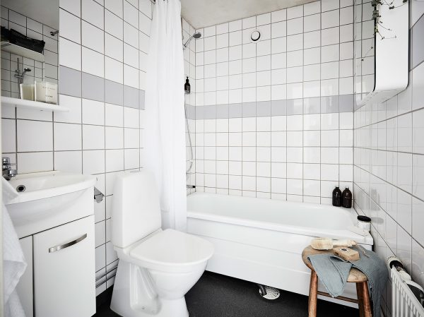 The Bathroom Echoes The Kitchen In A Wall Of Tiling With A Stroke Of Grey.  White Amenities, Shower Curtains And Cabinetry Offer Just Enough Space For  A ...