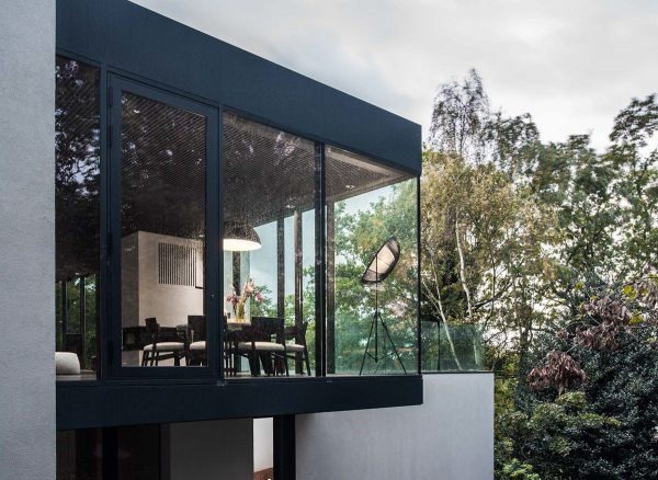 As the dining room looks over the forest the lounge beside uses green to penetrate three of its four walls muted grey block couches sit on simple