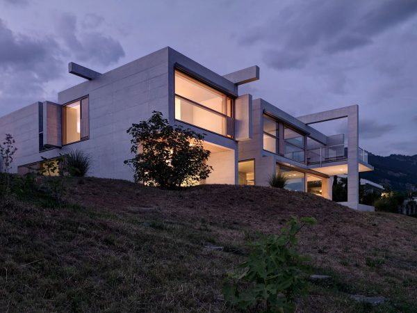 Anchored on the hilltop this stacked concrete creation glows invitingly from within the enormous windows tear across the solid box like design
