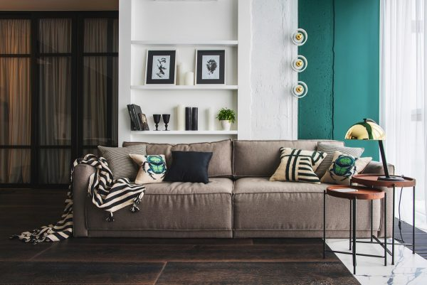 Taupe upholstery on a deep cushioned sofa works beautifully with the vivid blue green paint colour slightly neutralising its intensity