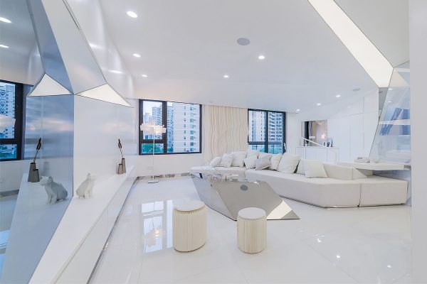 Angled cutaways in the wall and ceiling create plains for extra light sources which help bathe the arctic white room with brightness and reflection over