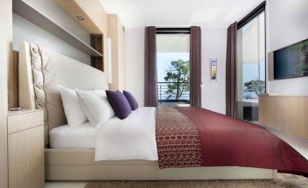 Một phòng ngủ khách cung cấp trang trí thanh thản và yên bình với những người trung lập và chỉ liên lạc của màu sắc ánh đỏ sẫm.