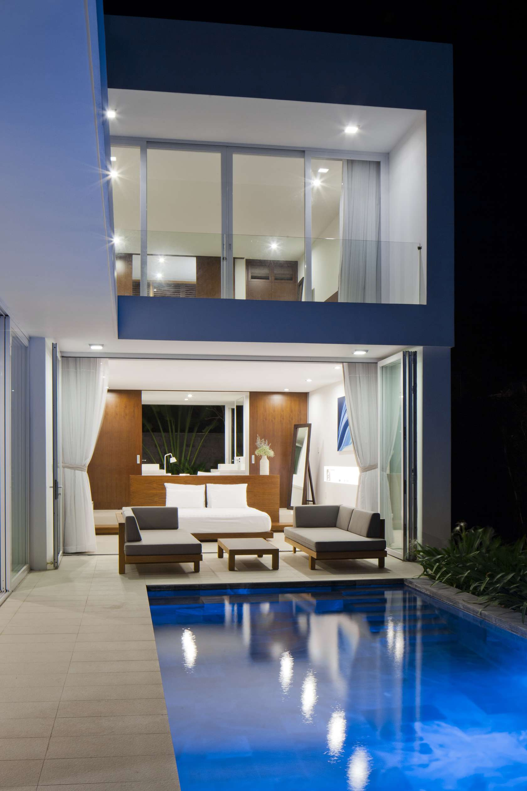 Beachfront Luxury Modern Home Exterior At Night: Private Beach Villas Offer Spectacular Ocean Views And Luxurious Interiors