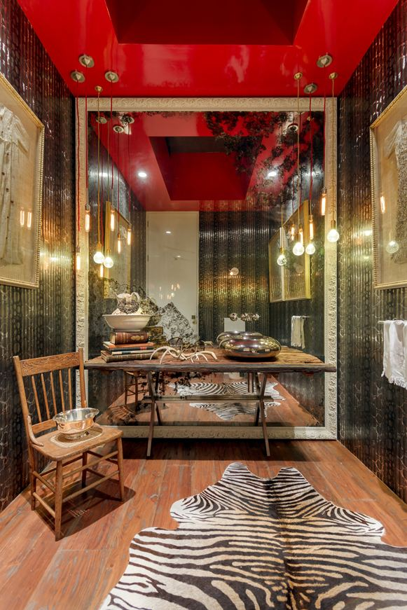 The kitchen is vibrant and pulsating with red accents colorful tiles and an open dining space that begs for visitors to stay a bit longer and have another