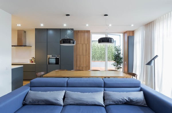 A bright blue sofa adds a playful splash of color to the living room and brings out the bluish hues blended into the gray cabinetry in the background