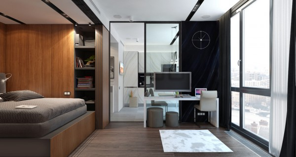 This space triples as an office living room and bedroom but the large windows and glass wall into the kitchen help this otherwise tiny space feel