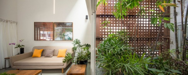 Modern furniture demonstrates a sense of orderliness that differentiates the interior from the central atrium but the potted plants reinforce the