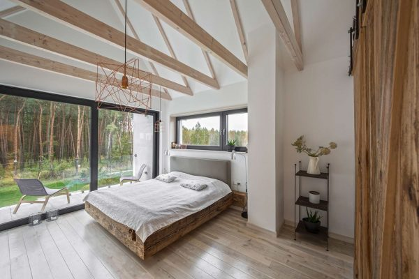 Forest while iron sliding barn doors extend to the corridors a distressed wooden bed frame black iron shelving and cobweb chandelier add character