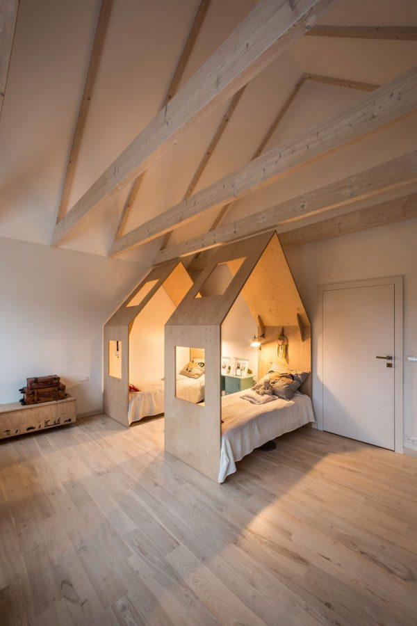 On the opposite side of the house parents sleep in rustic tones light wooden floors and trussing reveal an area made wide by both doors and sliding