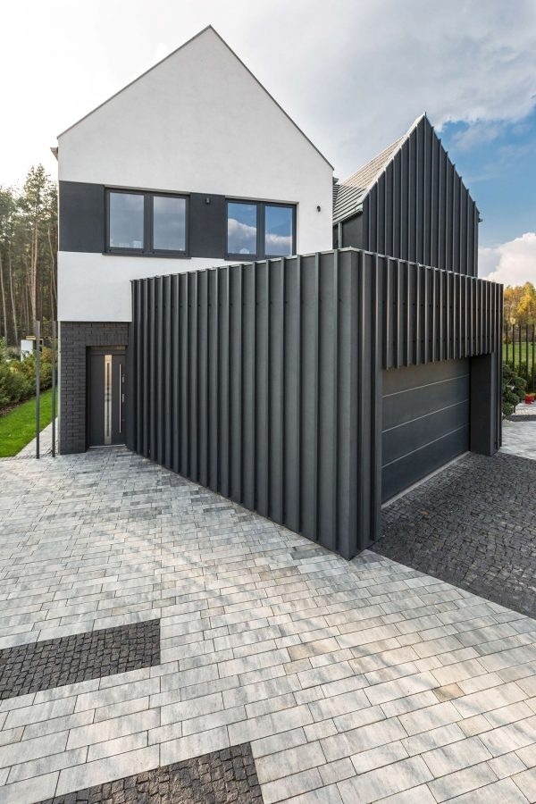 A drive up to the property reveals two traditional houses separated by one central garage clad in corrugated iron and plaster its look is contemporary