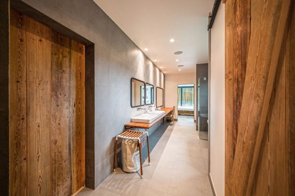 Two bathrooms show both adult and child personalities the master bathroom is slick and industrial featuring polished imperfect wood a simple glass
