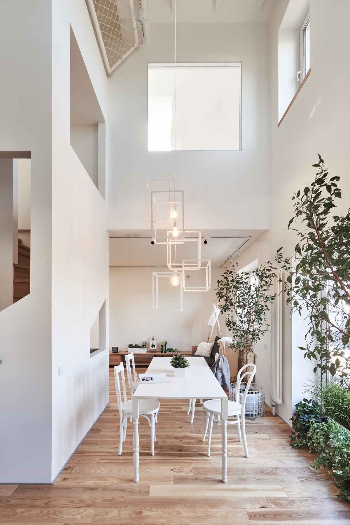 home designing a white and wood house for a stylish family decorative elements in the house are simple yet notable like the geometric dining room pendant light that hangs over the table