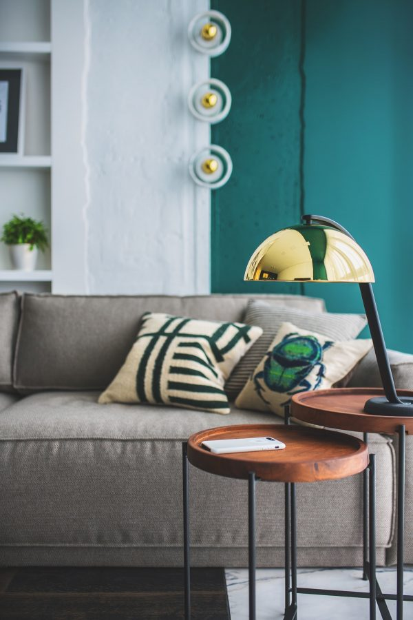 A pair of round wooden nesting tables hold a gold designer table lamp for use as a focussed task light on the sofa