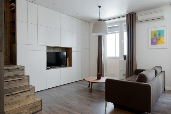 A bank of cabinets have been built around the television to house all of the couples other belongings the furniture and lighting in the apartment are by