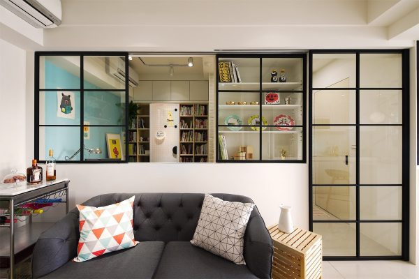 One side of the black aluminum framed window slides open over an adjacent recessed shelving unit the displaced glass appears as an attractive display